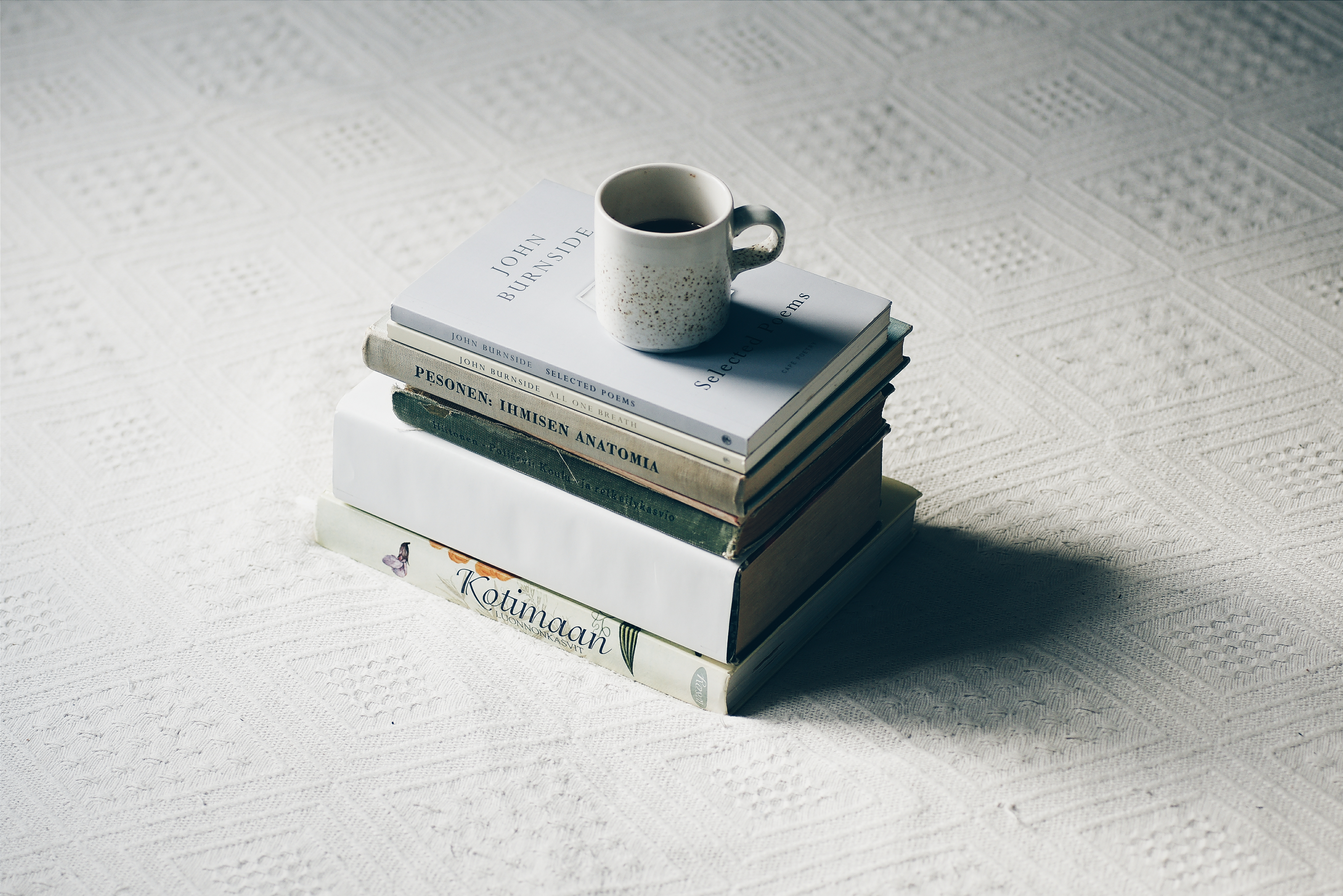 pile of books with a cup of coffee on top